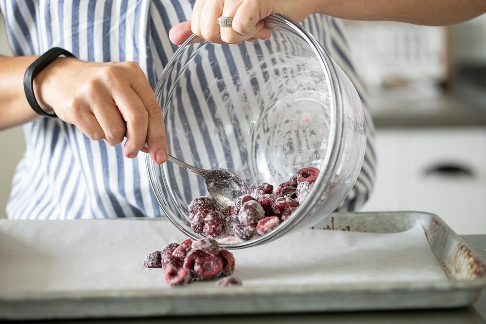 woman pouring cherries covered in sugar and cornstarch on parchment lined baking sheet.