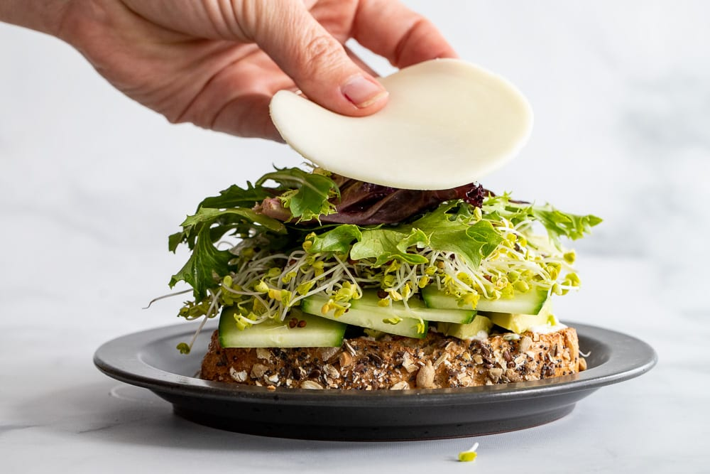 woman adding sliced provolone to sandwich