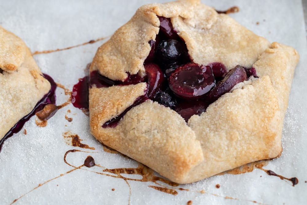 baked rustic blueberry and cherry galette on baking sheet
