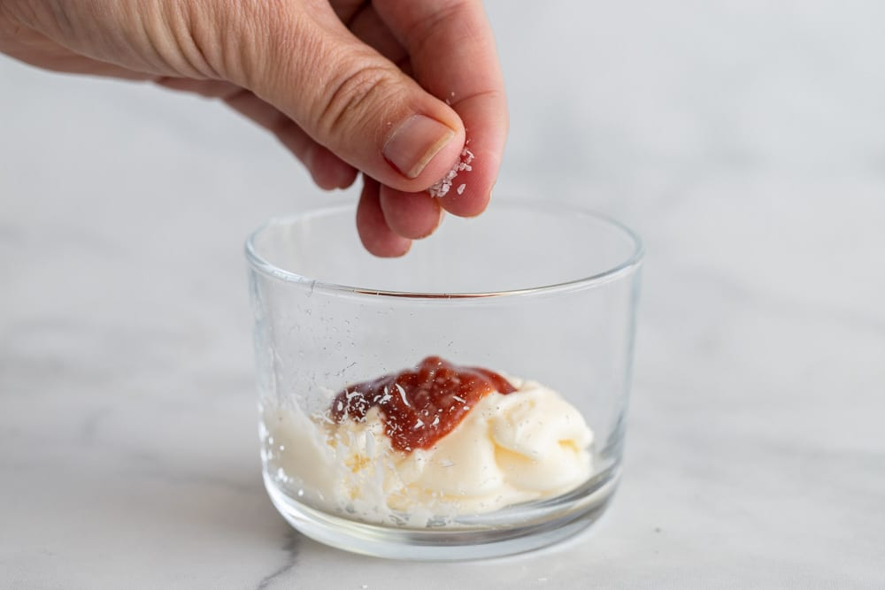 woman adding a pinch of salt to sriracha mayo in small glass container.