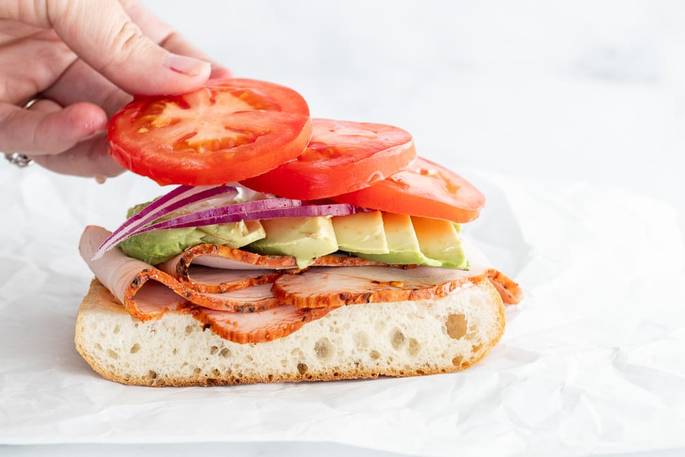 woman adding sliced tomatoes to sandwich
