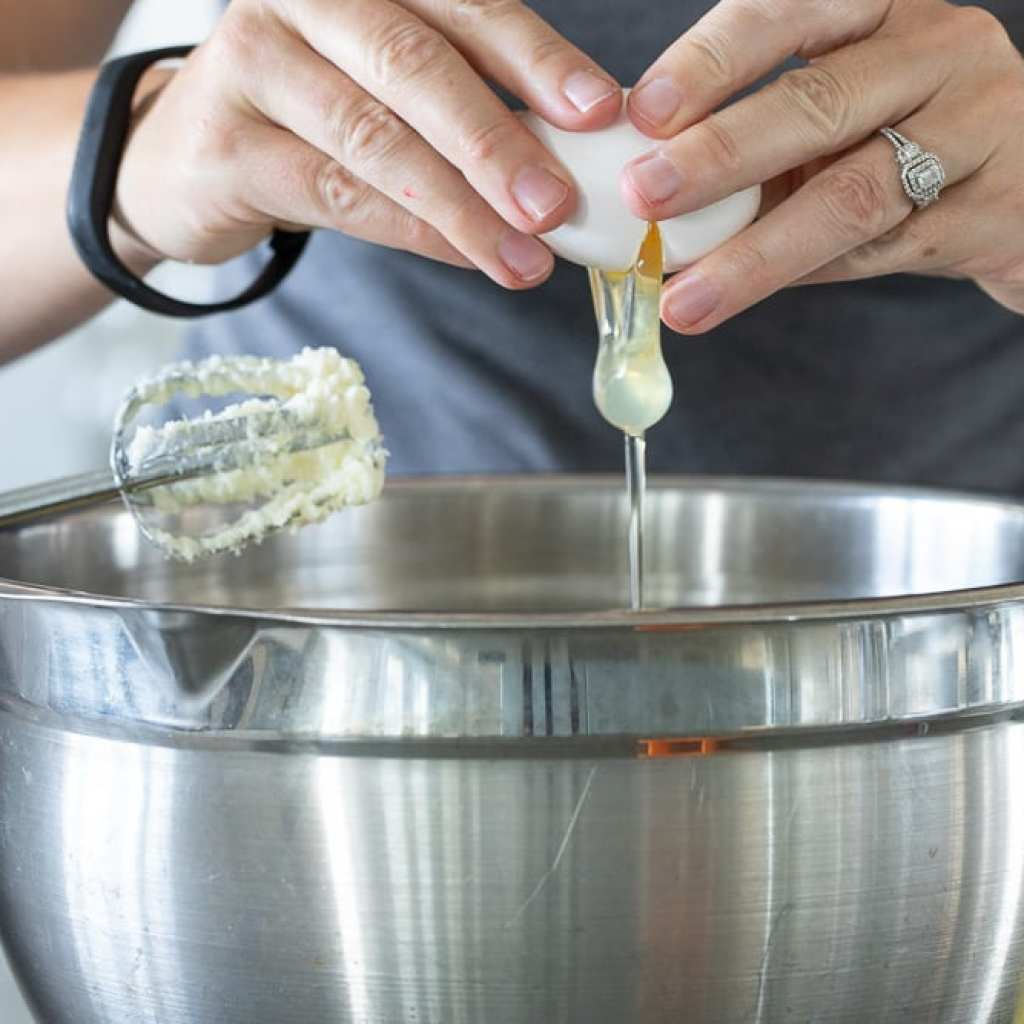 woman adding egg into stainless steel bowl