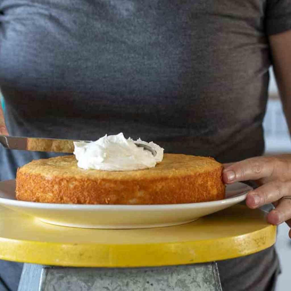 woman spreading lemon icing onto cake
