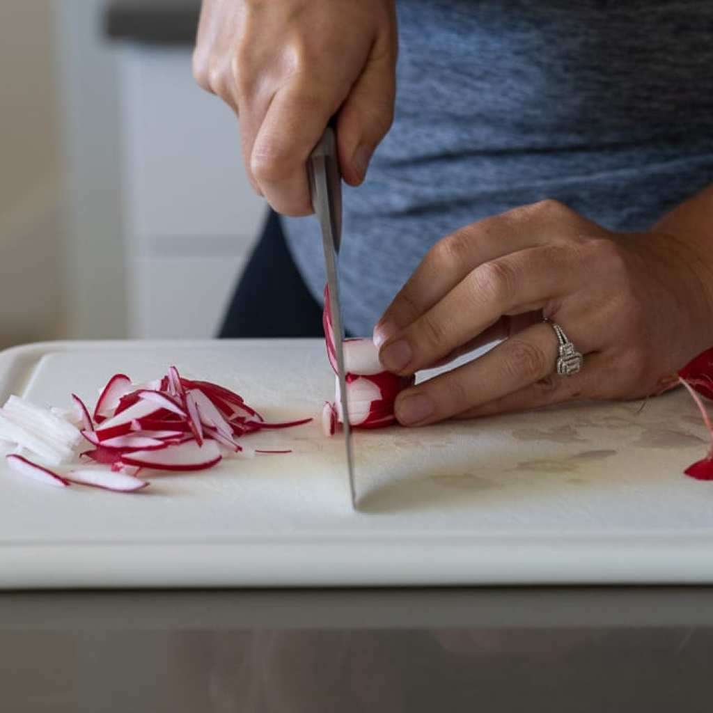 woman slicing radishes for banh mi sandwich