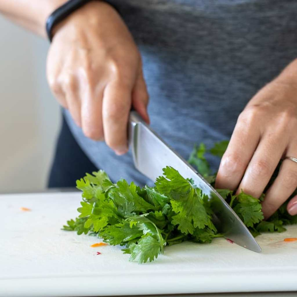 woman slicing cilantro for banh mi pork tenderloin sandwiches