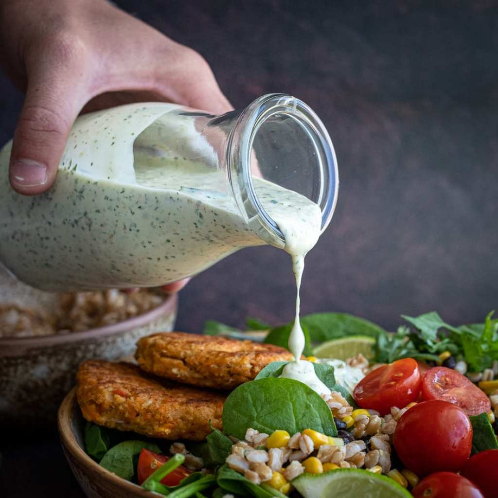 healthy salmon and grain bowl in ceramic pasta bowl. woman pouring jalapeno ranch over top