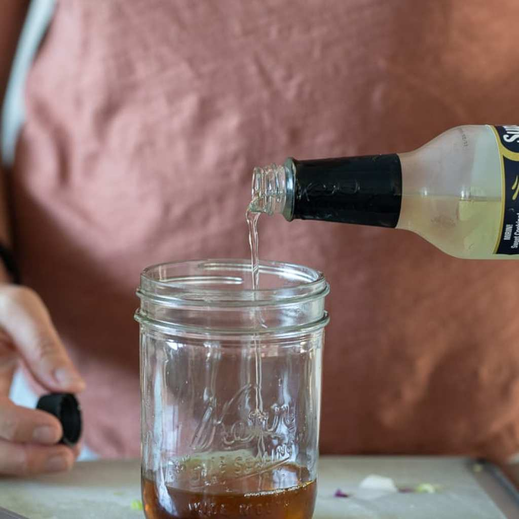 woman pouring rice vinegar into mason jar for dressing.