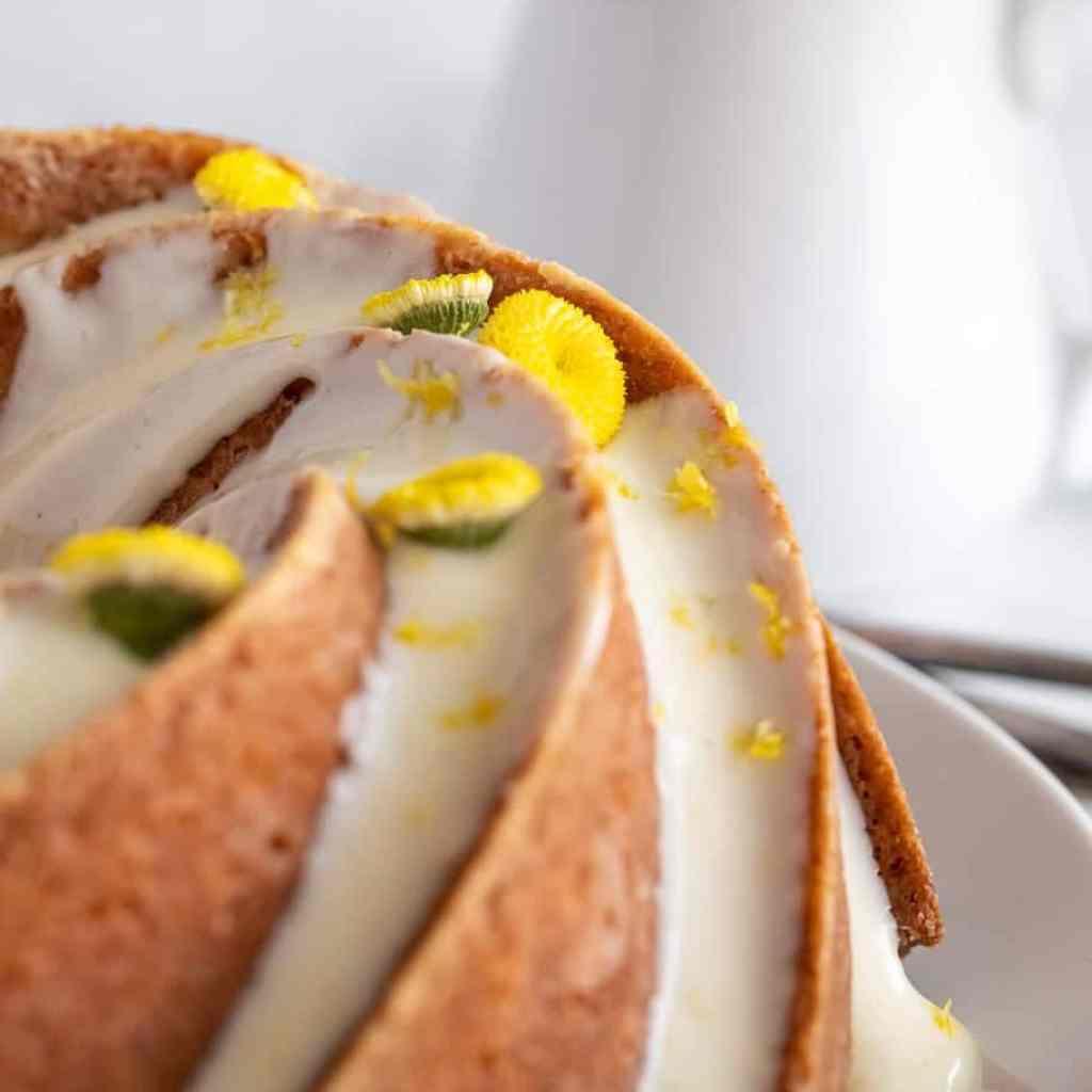 Lemon chamomile bundt cake topped with fresh chamomile flowers