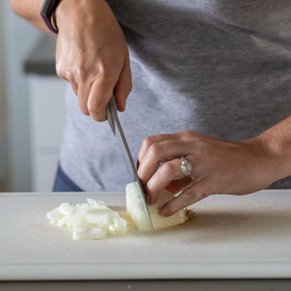 woman cutting onion with chef's knife on a plastic cutting board