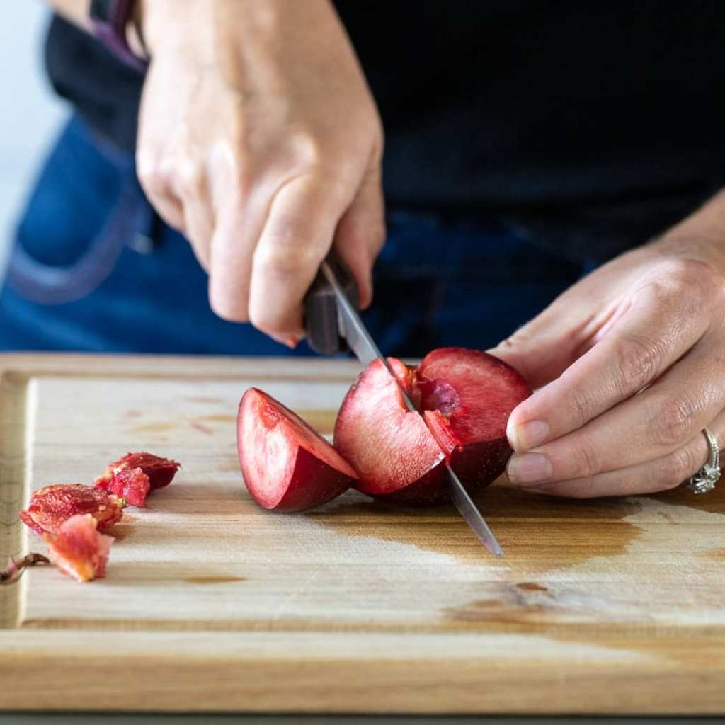 woman cutting plums to roast on wooden cutting board