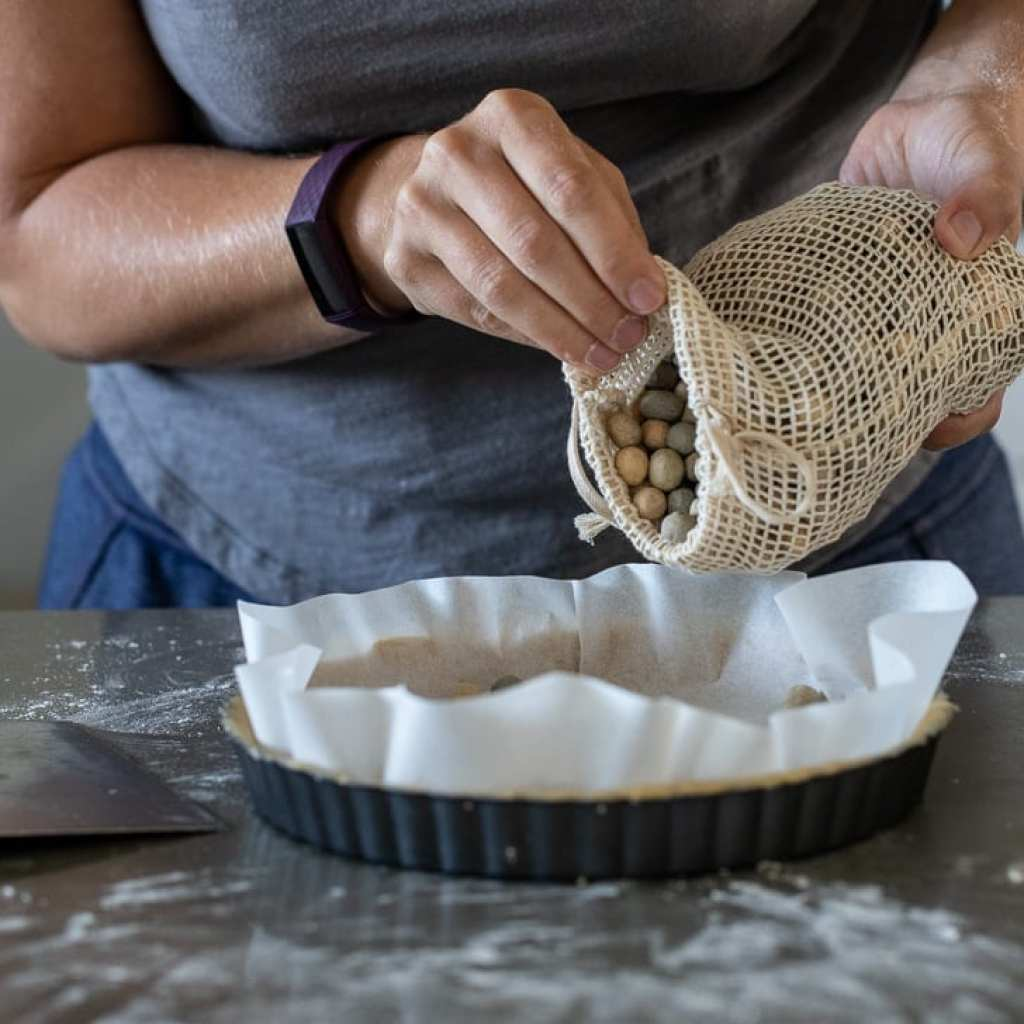 woman adding pie weights to tart for blind baking