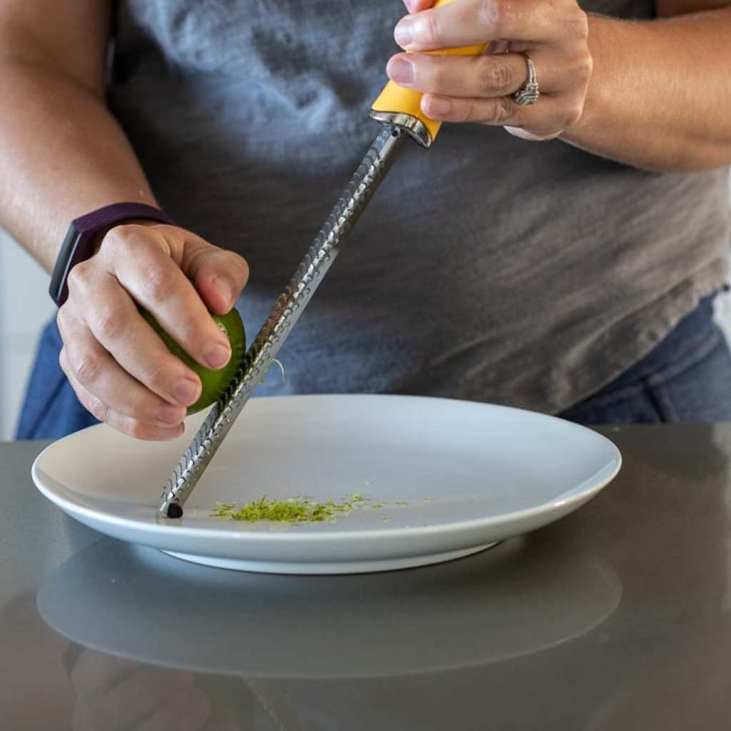 woman zesting a lime over a white dinner plate
