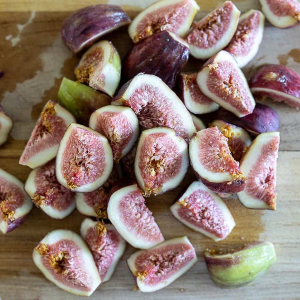 figs quartered on wood cutting board