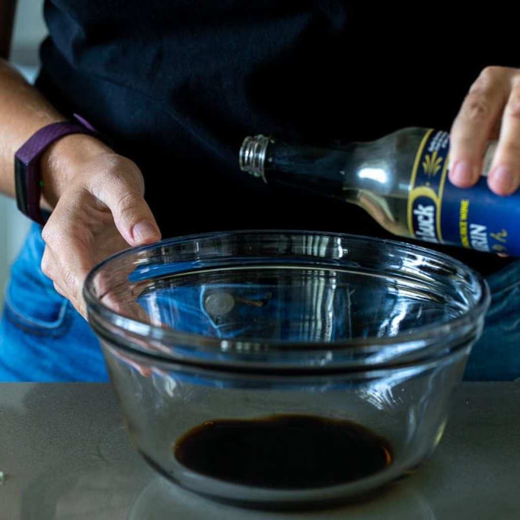 woman adding rice vinegar to clear glass bowl