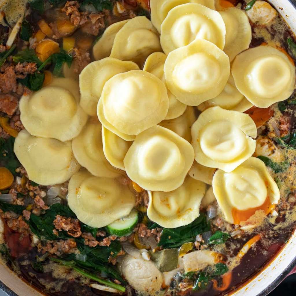Cozy Sausage and Ravioli Soup cooking in enamel Dutch oven