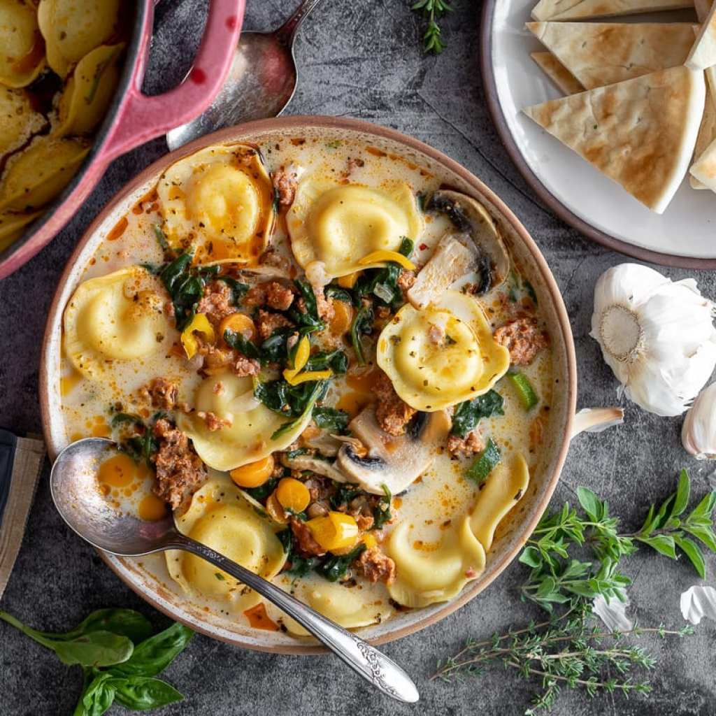 Cozy Sausage and Ravioli Soup in ceramic bowl with ingredients on the surface