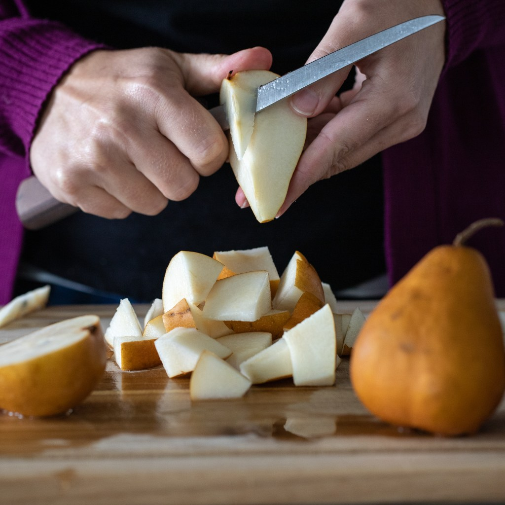woman cutting up pears for fruit salad