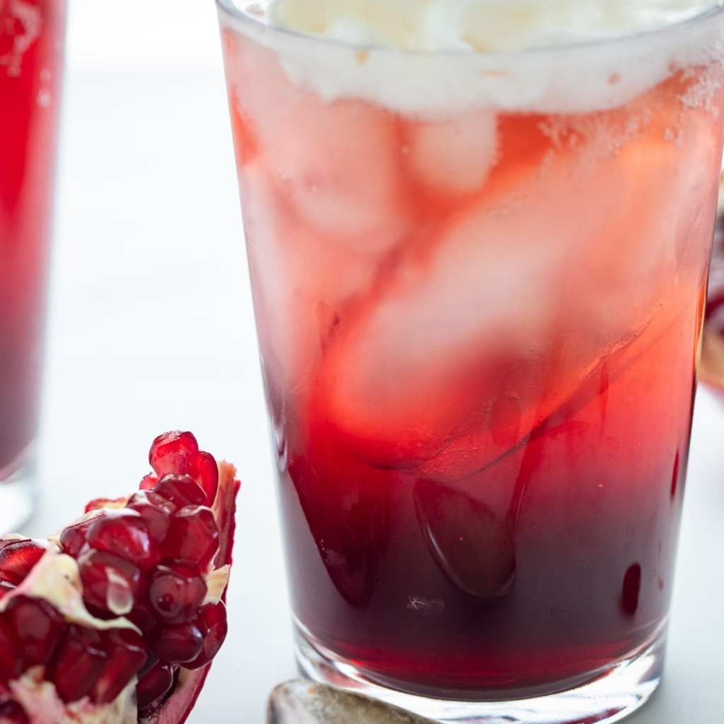 layers of pomegranate and vanilla cream in clear glass cup