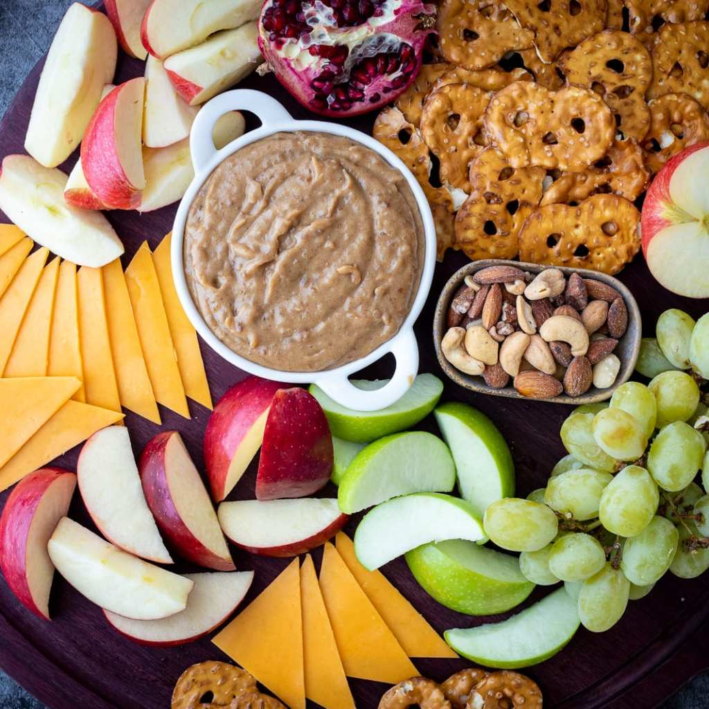 date caramel and peanut butter dip on a charcuterie board with sliced apples, cheese, pretzels, and grapes