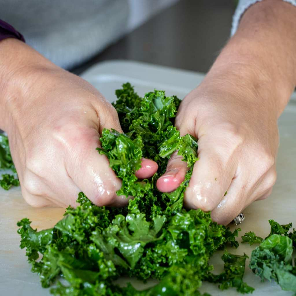 woman massaging kale for autumn salad