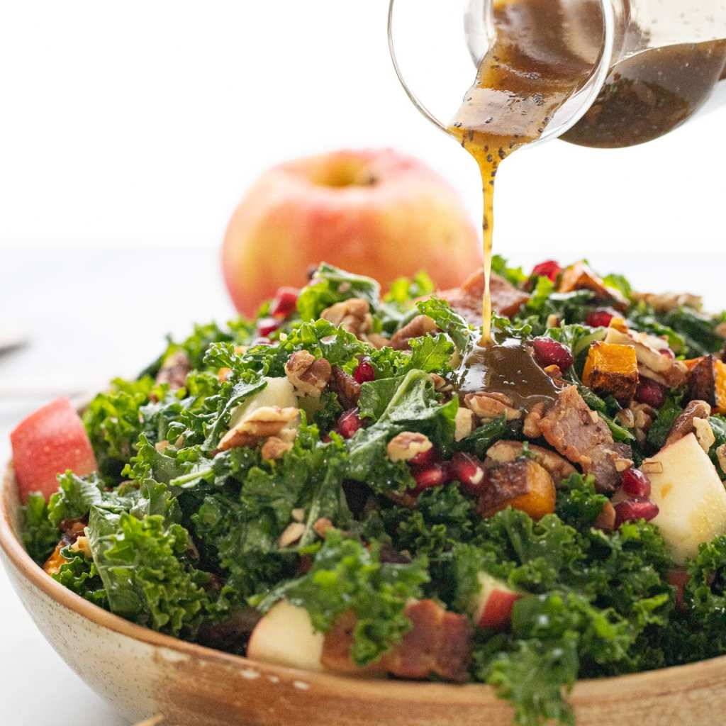 Autumn Kale Salad with Butternut Squash in a ceramic bowl with a maple poppyseed dressing