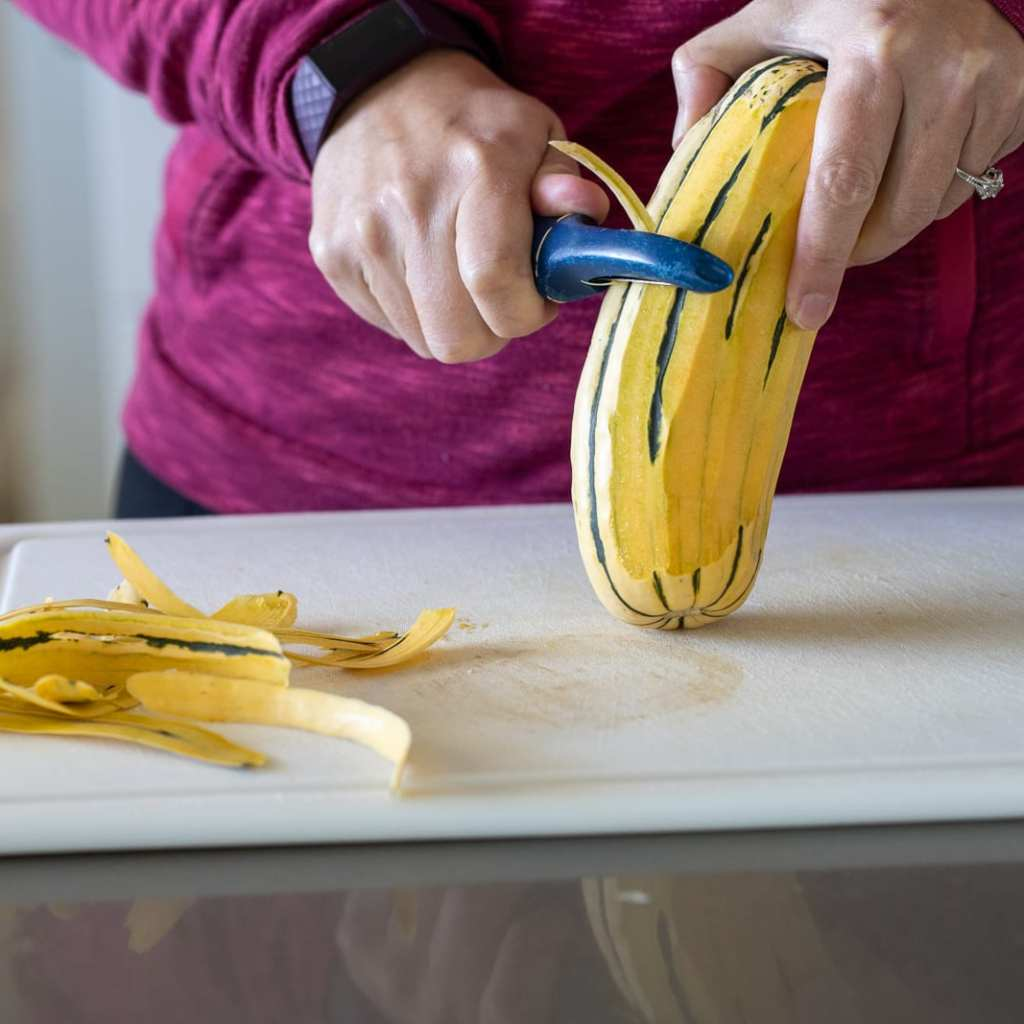 woman peeling a delicata squash with a vegetable peeler on a white cutting board