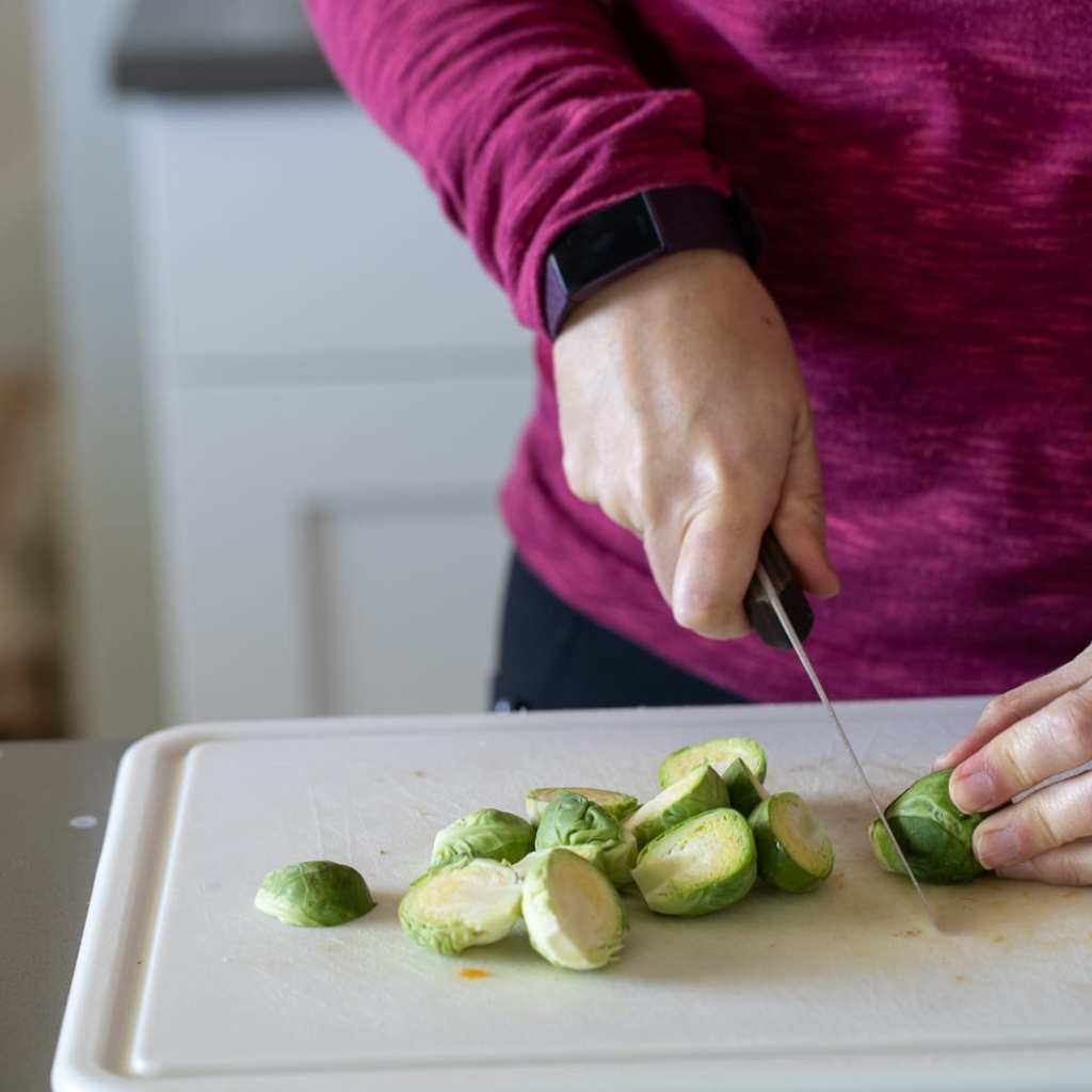 woman cutting up brussel sprouts for salad