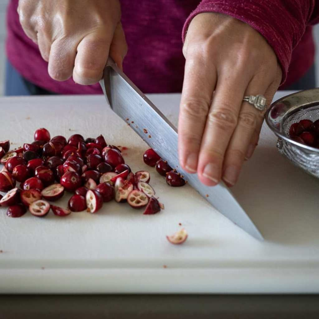 woman cutting fresh cranberries on white cutting board with a chef's knife