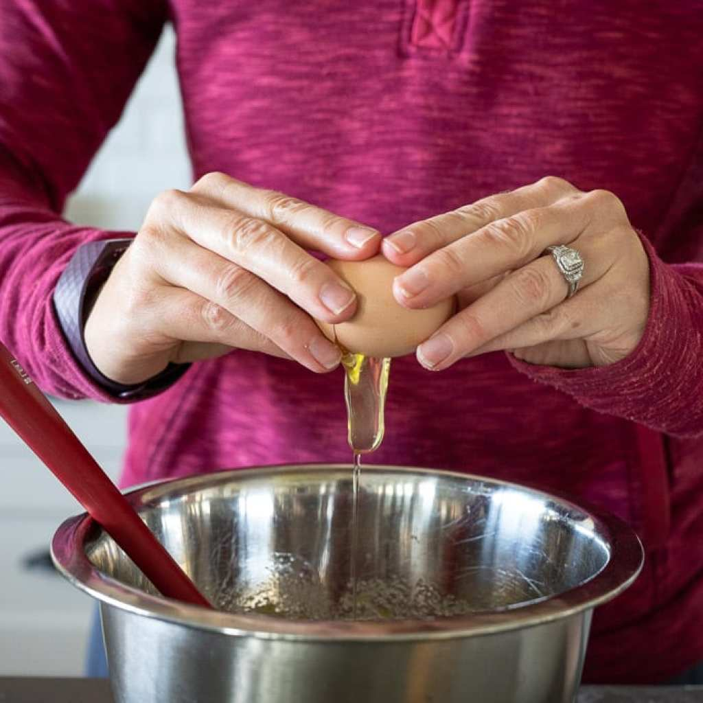 woman cracking an egg into a stainless steel bowl for making fresh cranberry orange muffins