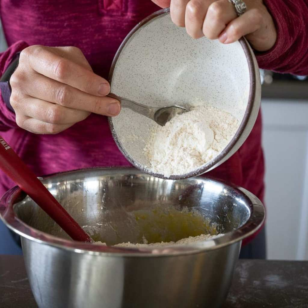 woman adding flour mixture to cranberry orange muffins from ceramic bowl into stainless steel bowl