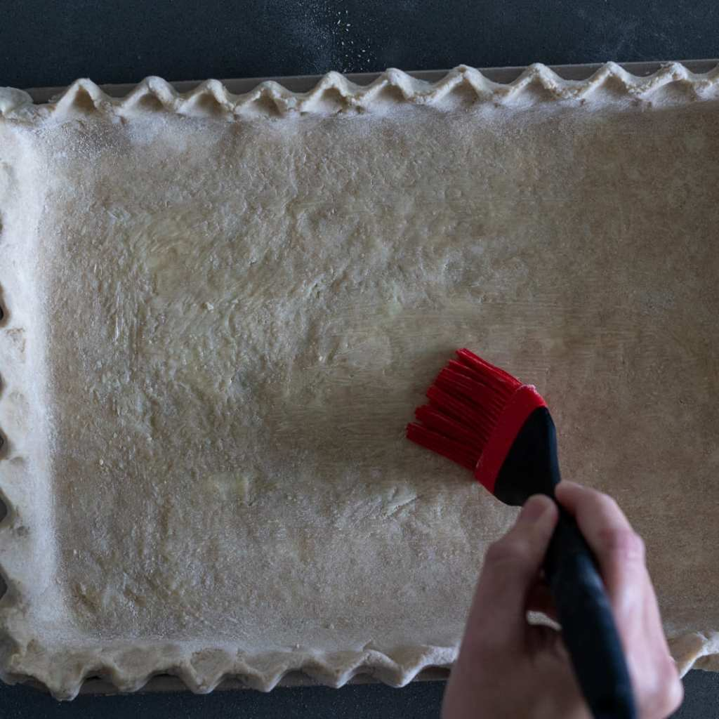 woman brushing melted butter on a slab pie