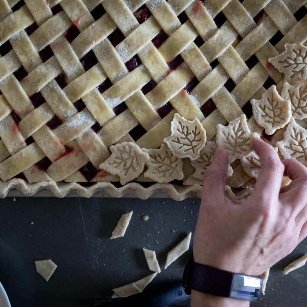woman adding leaf decorations to a lattice work cherry slab pie