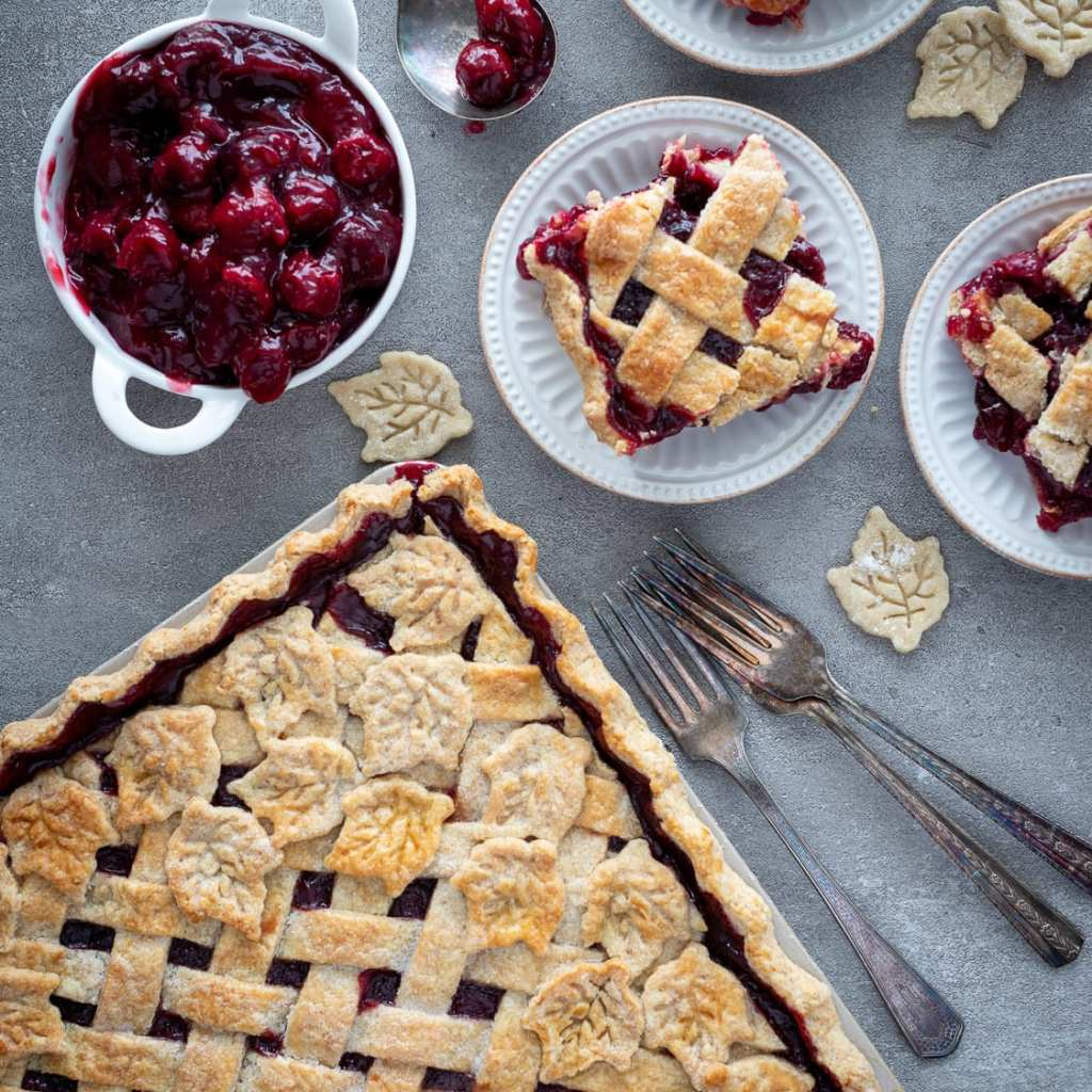 Beautiful Cherry Slab Pie on  slate surface with slices of pie on small white plates and antique forks on the side