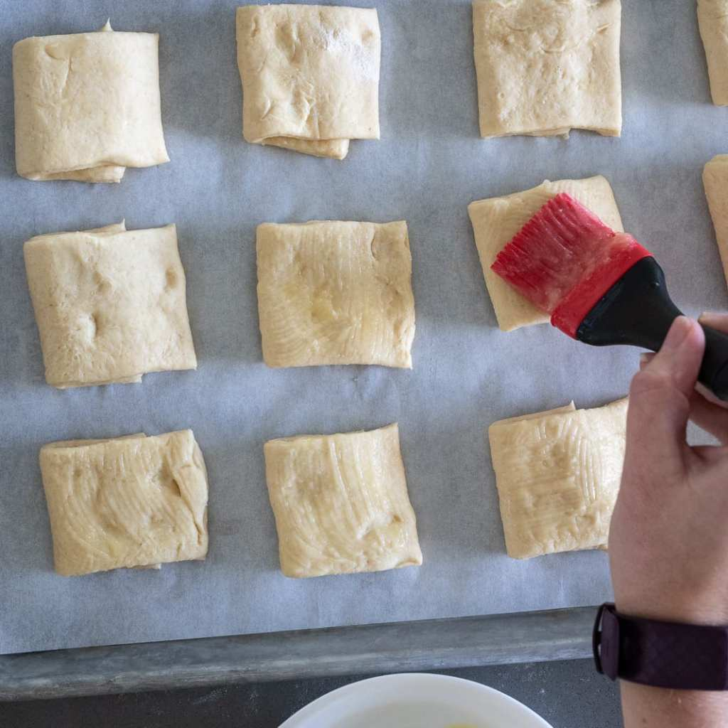 woman brushing parker house rolls with honey butter on a parchment-lined baking sheet