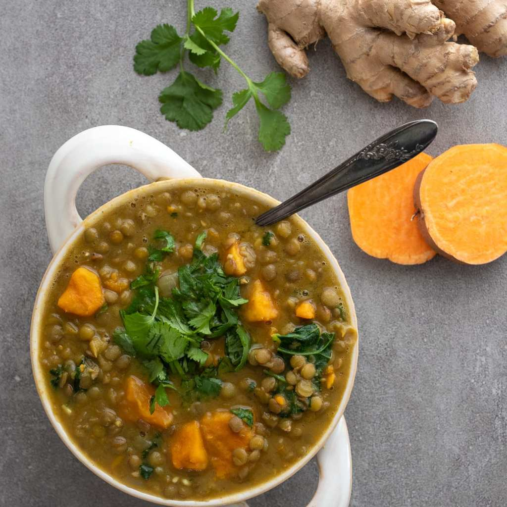 Simple Lentil and Sweet Potato Soup on slate surface with ginger, sweet potatoes and cilantro