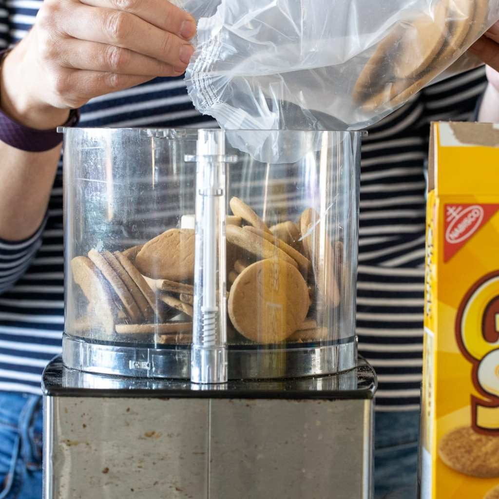 woman adding gingerbread cookies to food processor to make gingerbread truffles with.