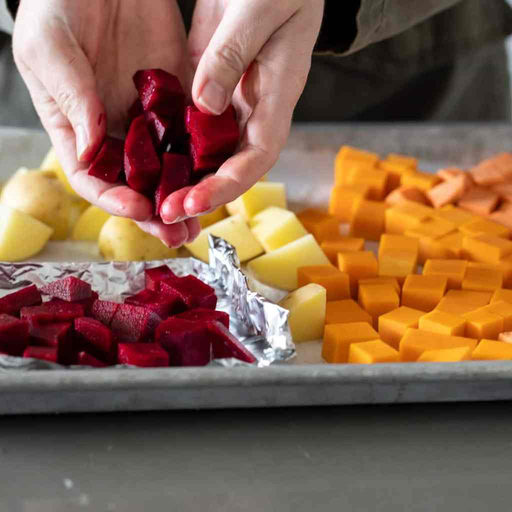 woman placing beets to small tinfoil boat on baking sheet