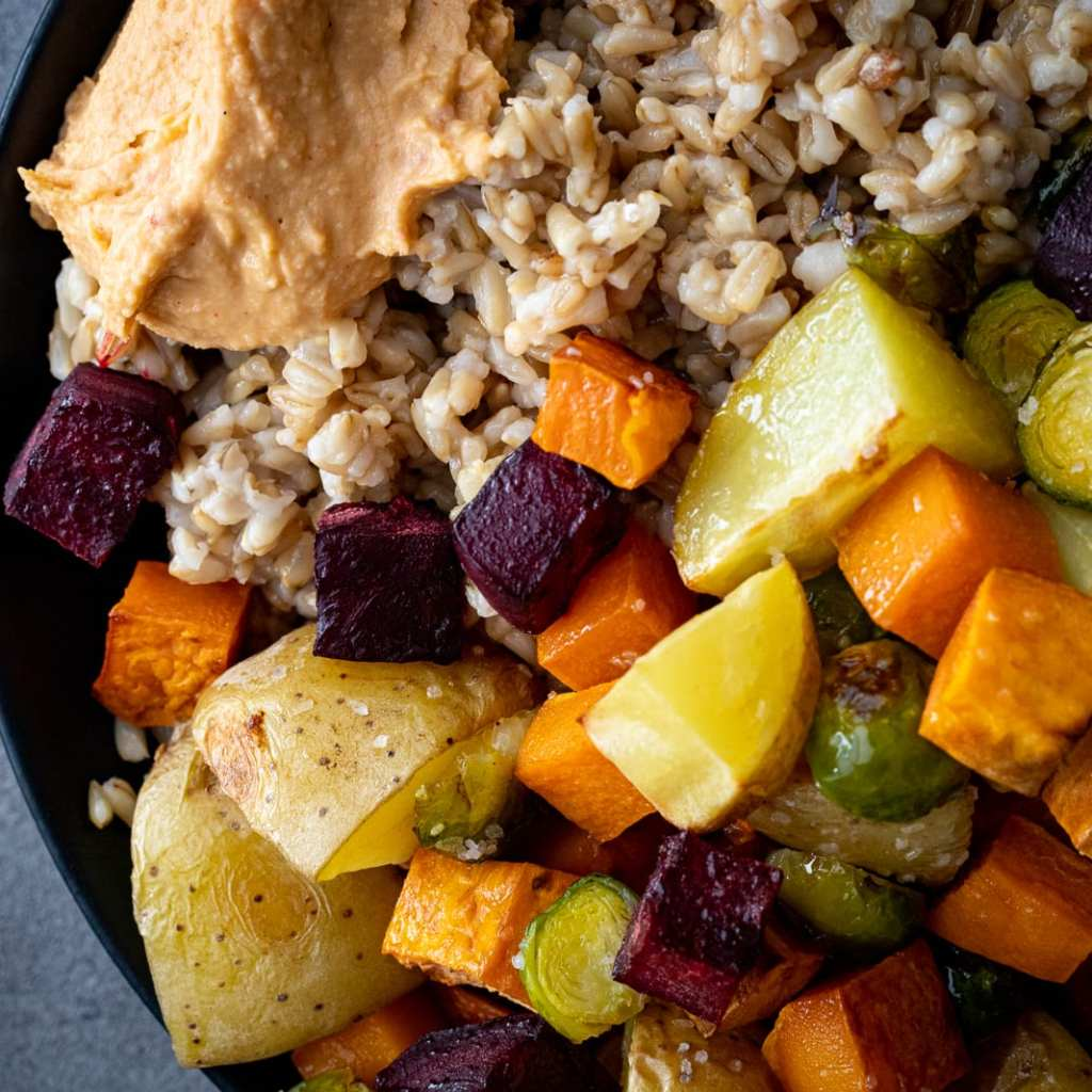 Gluten-free vegetarian grain bowl with roasted red pepper hummus
