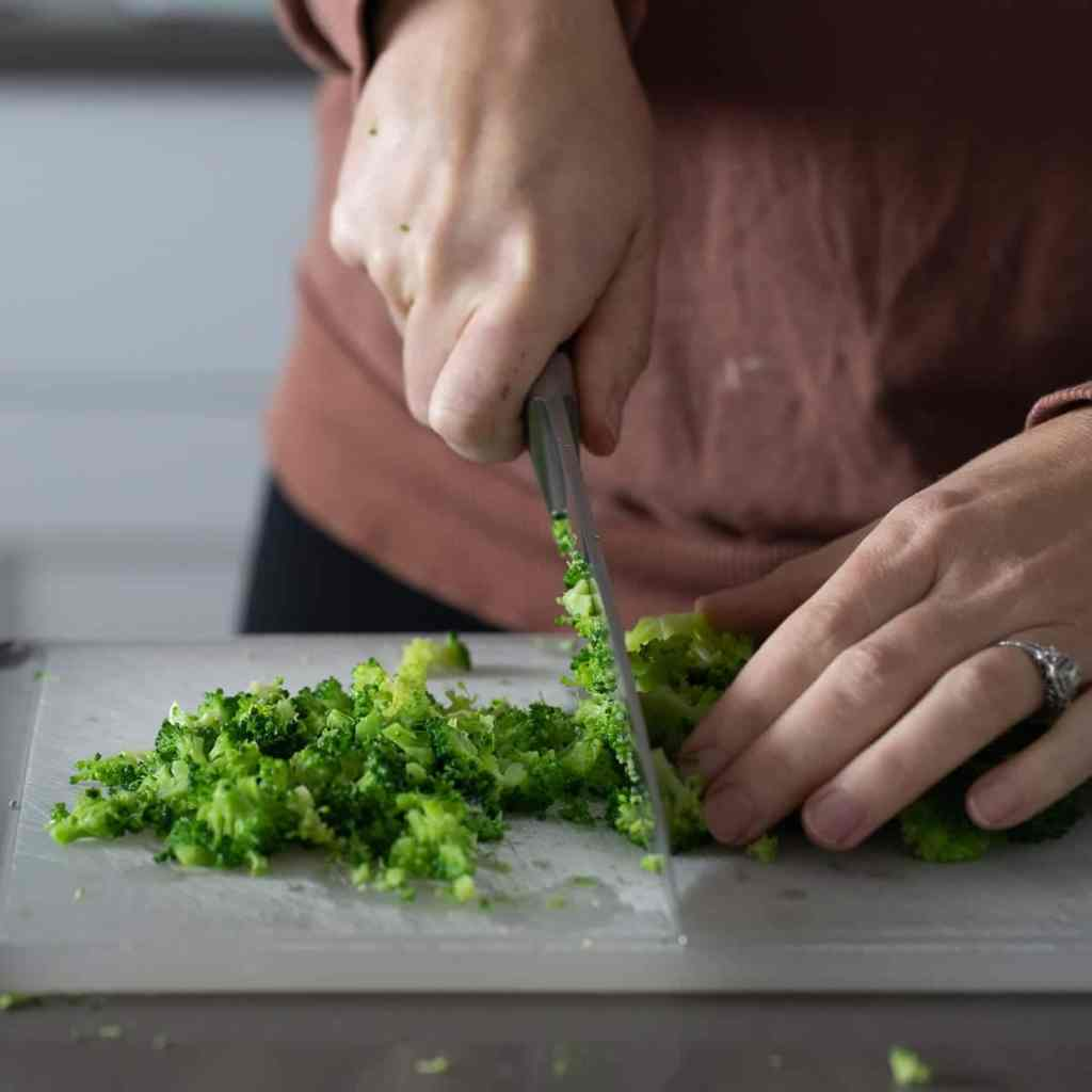 woman chopping broccoli on a plastic cutting board for fritters