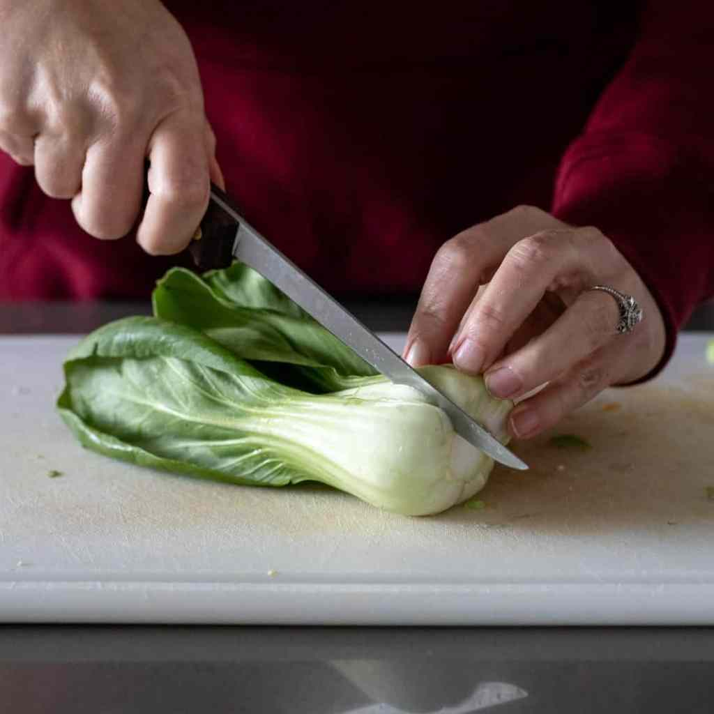 woman cutting bok choy in half on a white cutting board