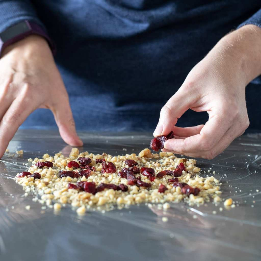 woman adding craisins, walnuts, and pepitas to saran wrap