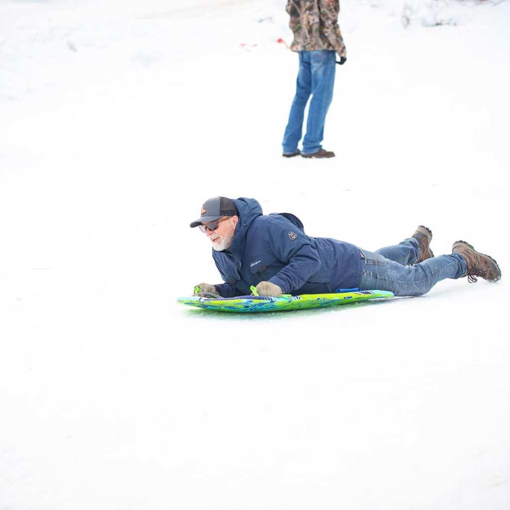 man on foam sled, sledding down sledding hill