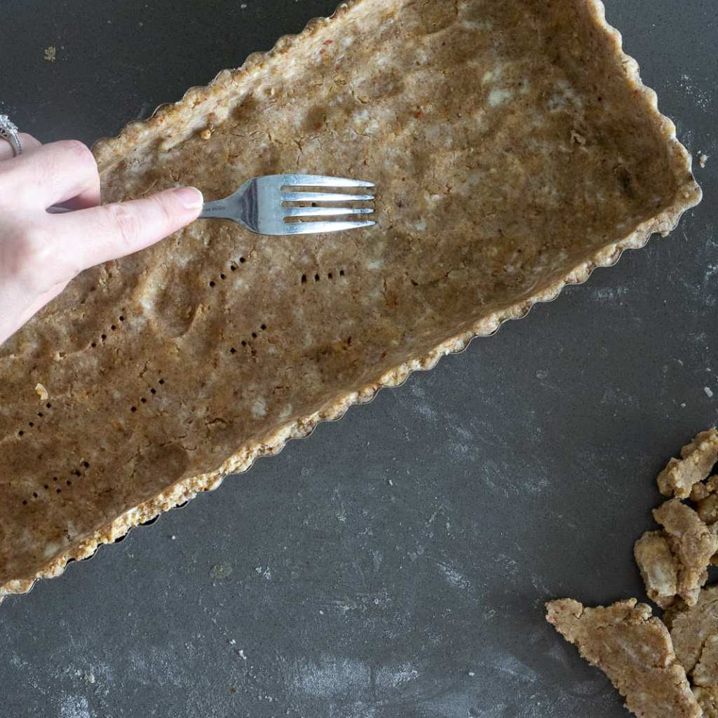 woman pricking almond tart shell with fork preparing for baking