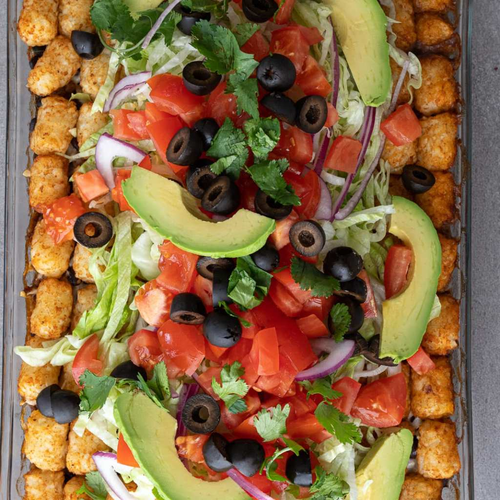 Simple Taco Tot Casserole layered with lettuce, olives, avocadoes. tomatoes and cilantro