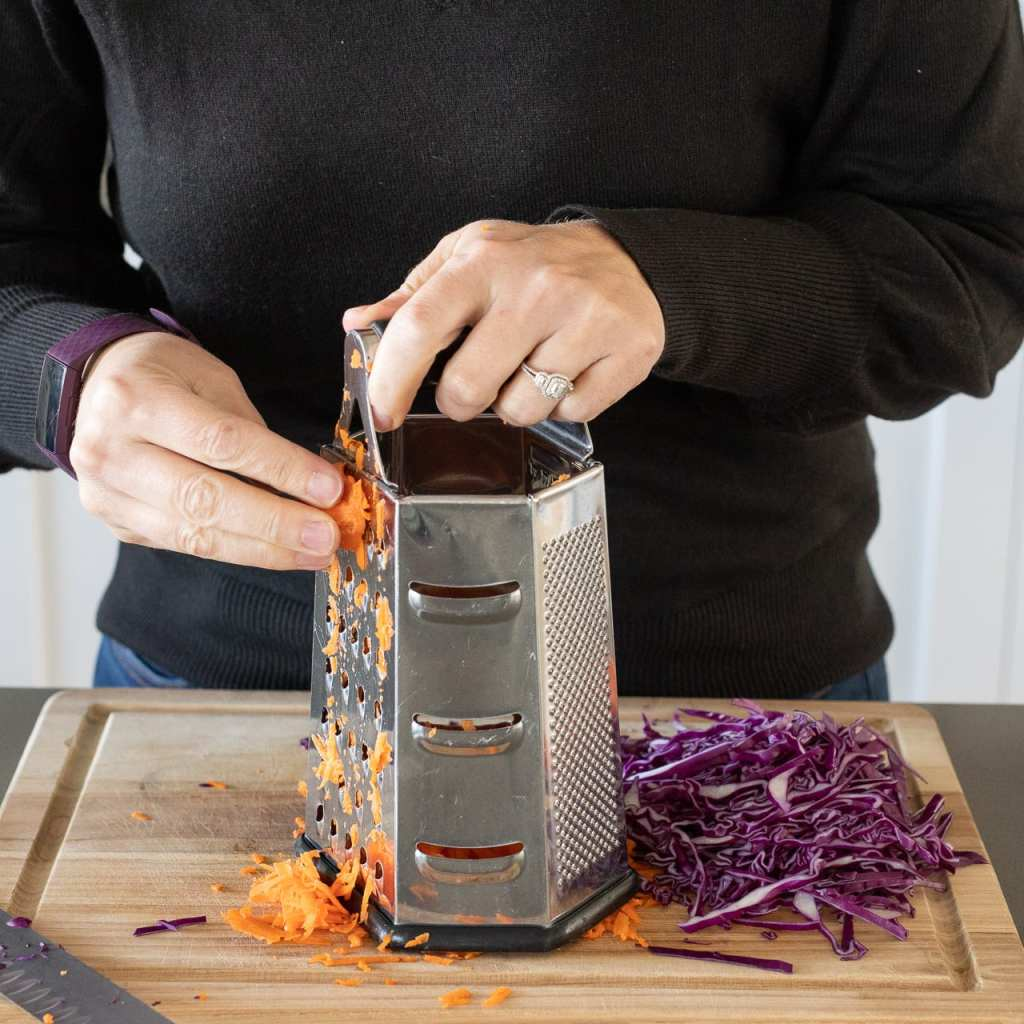 woman grating carrots on with a metal grater on a wood cutting board