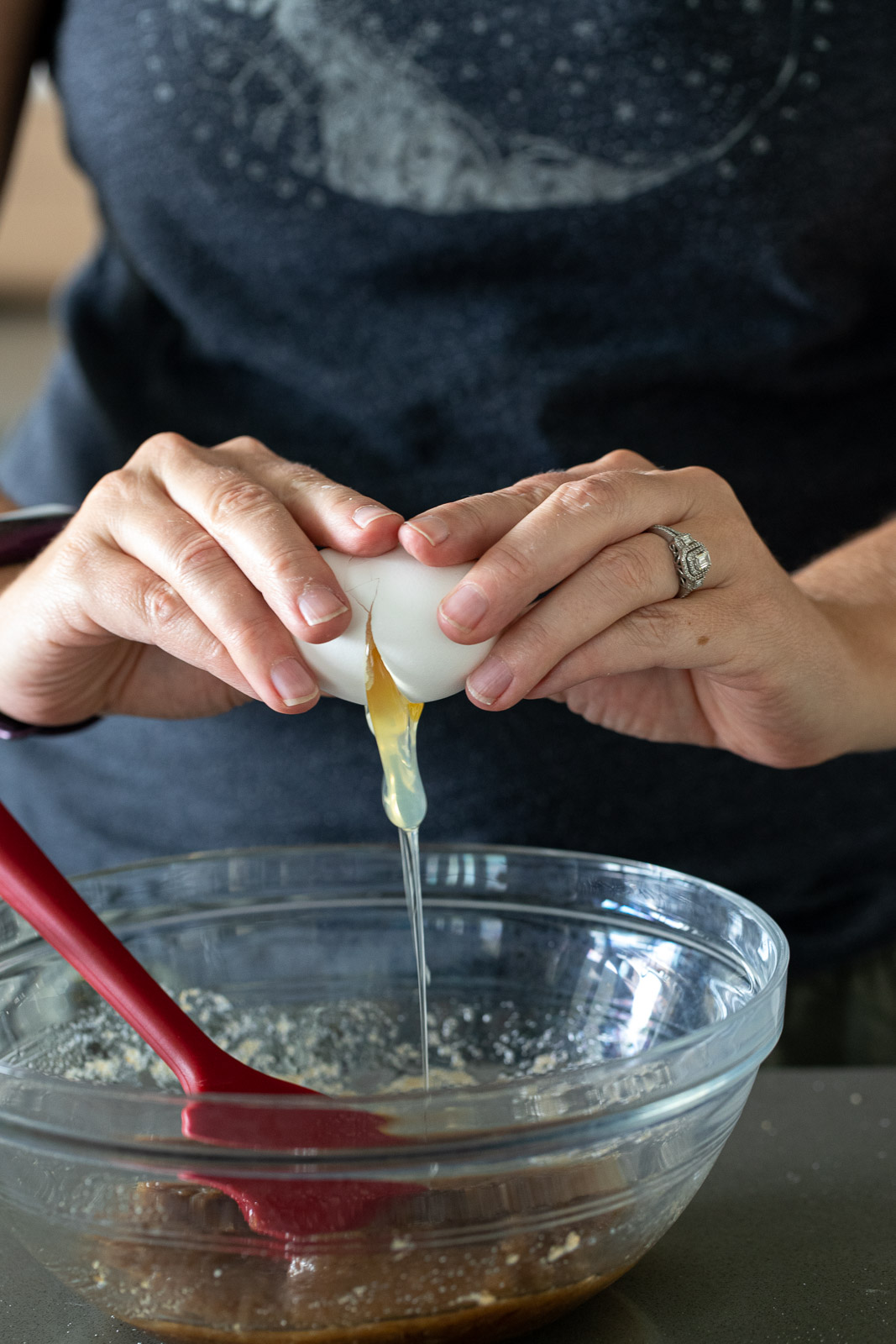 woman cracking an egg into a glass bowl.