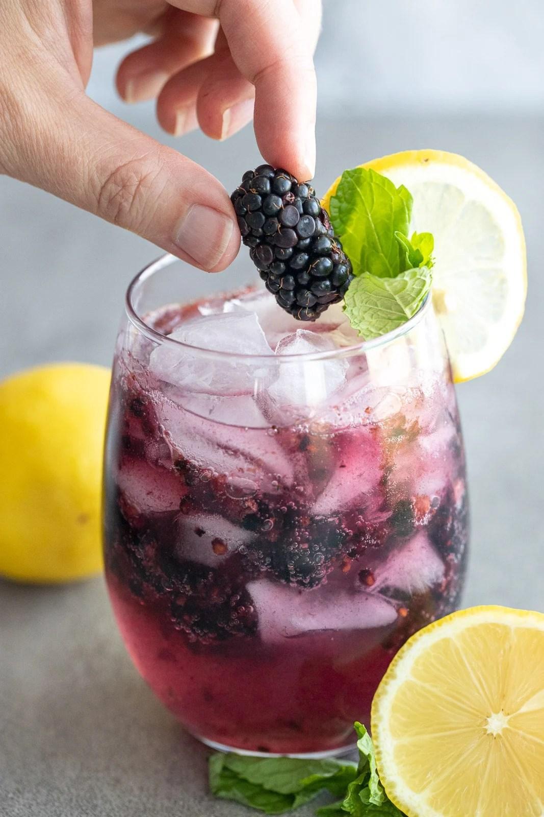 Woman adding a blackberry onto a non-alcoholic blackberry mojito.