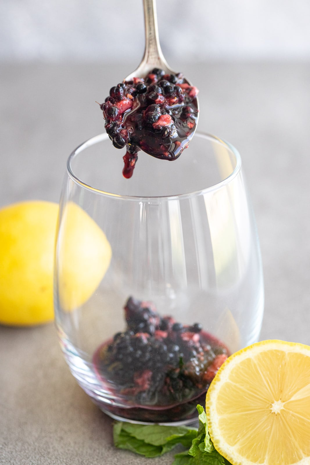 woman spooning a blackberry mix into glass cup.