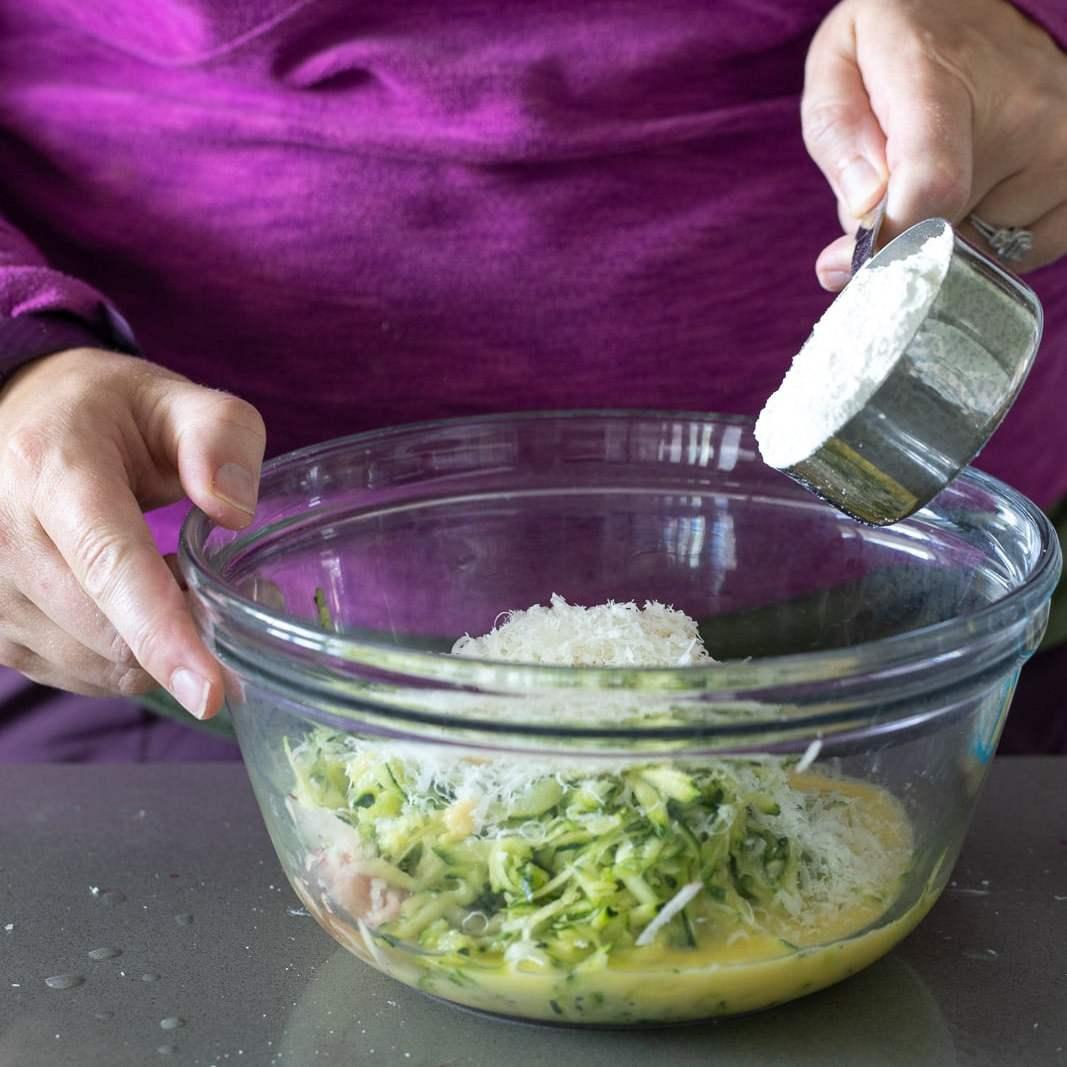 woman adding whole wheat flour to a zucchini potato fritter mix.