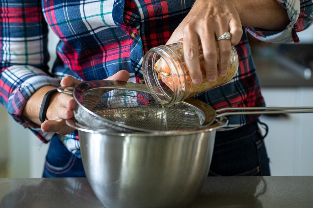 Woman pouring canned salmon into a mesh strainer.